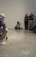 Hal Willner crouches to play with the Ginsberg bobblehead