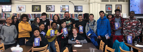 Author Mark Oshiro pictured with students holding his book Anger is a Gift