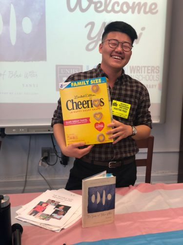 Photo of poet Yanyi holding a box of Cheerios